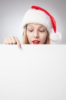 Красивая рождественская женщина в новогодней шапке, указывая пустую доску, изолированную на белом фоне