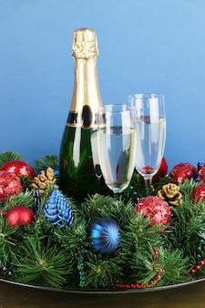 青い背景にシャンパンと構成の美しいクリスマスリース