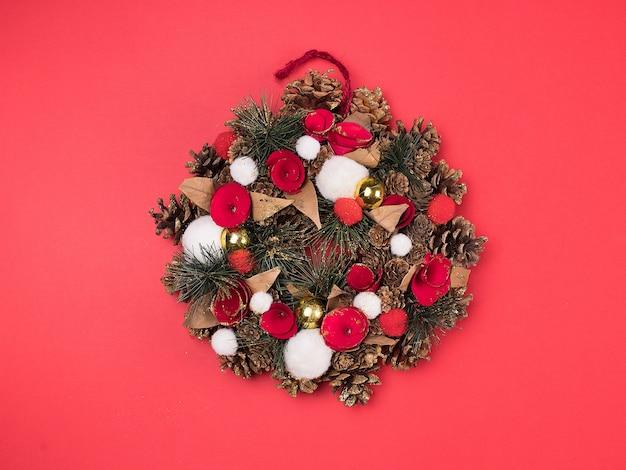 赤い背景の美しいクリスマスリース。素晴らしいデザイン