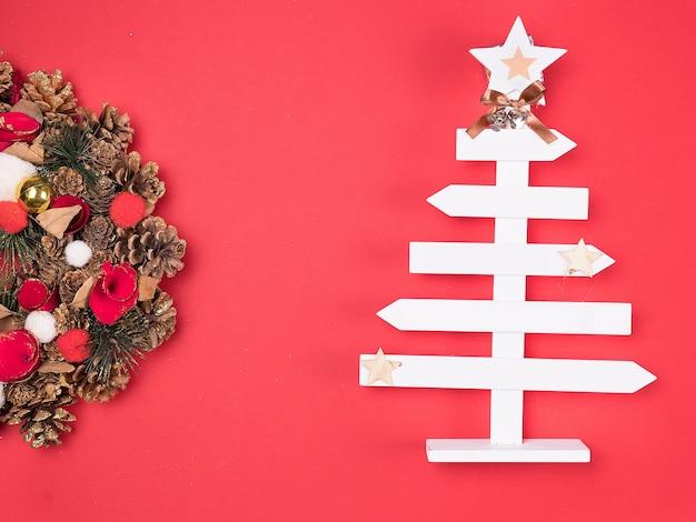 赤い背景に美しい家の装飾と美しいクリスマスリース。お祝いのインテリア