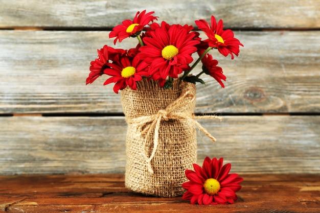 Красивые хризантемы в вазе на деревянных фоне