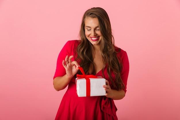 미소하고 선물 상자를 들고 빨간 드레스를 입고 아름다운 통통한 여자 20 대