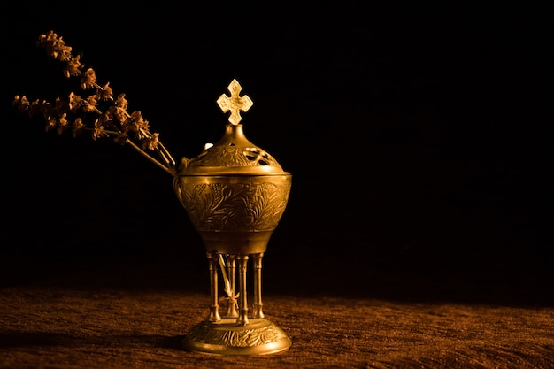 Beautiful church censer with a dried branch on black
