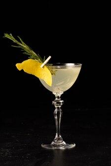 Красивый цитрусовый алкогольный коктейль, украшенный цедрой апельсина и розмарином в прозрачном бокале на темном фоне
