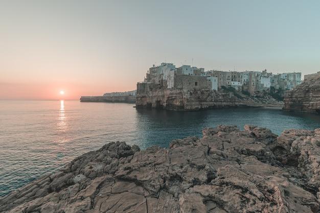 背景の夕日と海沿いの崖の上の美しい街