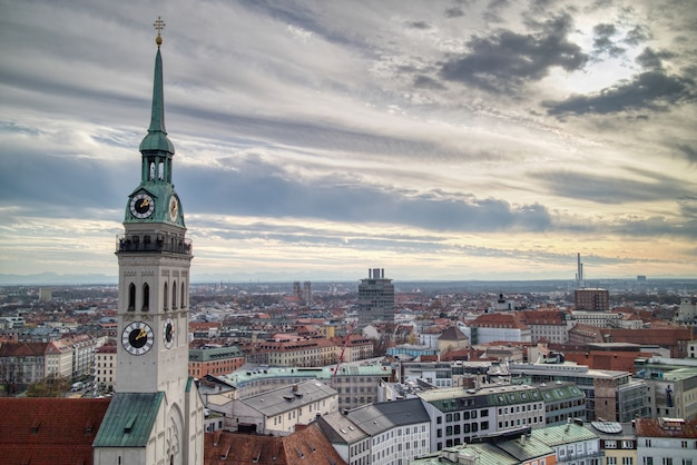 Beautiful cityscape aerial panoramic view above roofs of old houses historical part of munich, germany on a background of cloudy sunset sky.