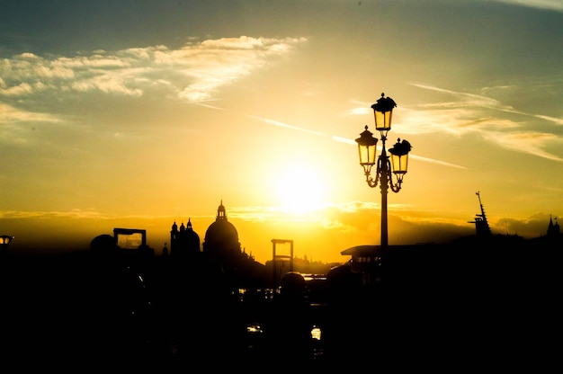 Beautiful cityscape with silhouettes of a street lamp and buildings in the sunset