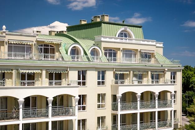 Красивое здание в классическом стиле с арочными балконами и зеленой металлической крышей.