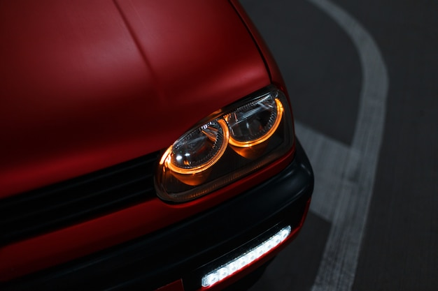 Beautiful classic red car with bright led headlights in the night city