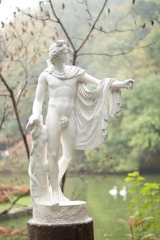 ギリシャまたはローマの神の美しい古典的な庭の像は、湖の前に立っている見事な裸の体格と流れるような衣服を持っています