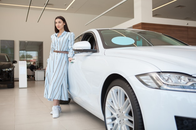 自動車販売店、コピースペースで彼女の新しい自動車の近くに立っている美しい上品な女性