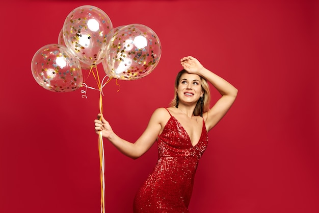 Beautiful classy young woman wearing low neck red dress posing and holding balloons