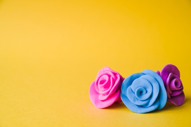 Beautiful clay roses on yellow backdrop