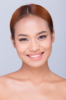 Красивая чистая кожа азиатская женщина с прямыми черными волосами с руками, руками, пальцами, лицом, поза, открытое плечо, улыбка, студийное освещение, белый фон, копия пространства, для рекламы ухода за кожей