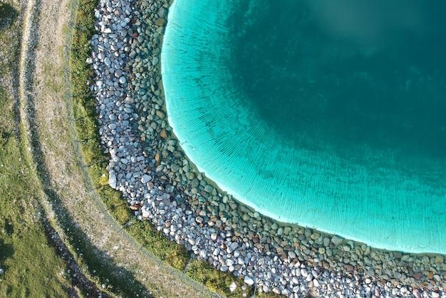 Красивое ясное голубое озеро в зеленом поле снято сверху