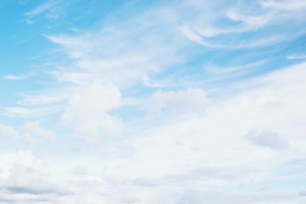朝の時間光線の日光に小さな無地の白い雲と美しい澄んだ青い空の背景。テキスト用のスペース。ソフトフォーカス。