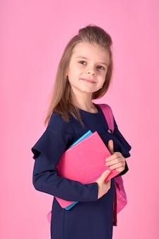 Красивая умная девушка с ноутбуком в школьной форме и розовом ярком рюкзаке