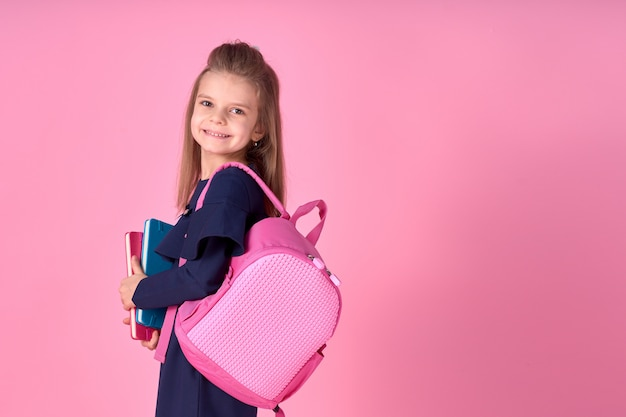 Beautiful clever girl with notebook wearing school uniform dress and pink bright backpack