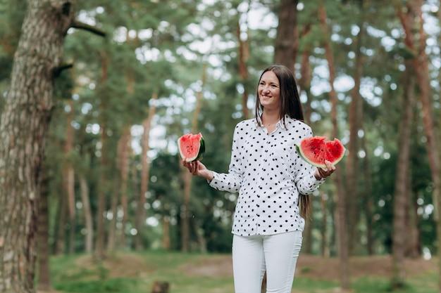 公園でスイカと、若いモデルの女性の美しいクローズアップの肖像画。スイカのスライスを保持しているかなりブルネットの少女。健康食品と幸せな夏の休日のコンセプト