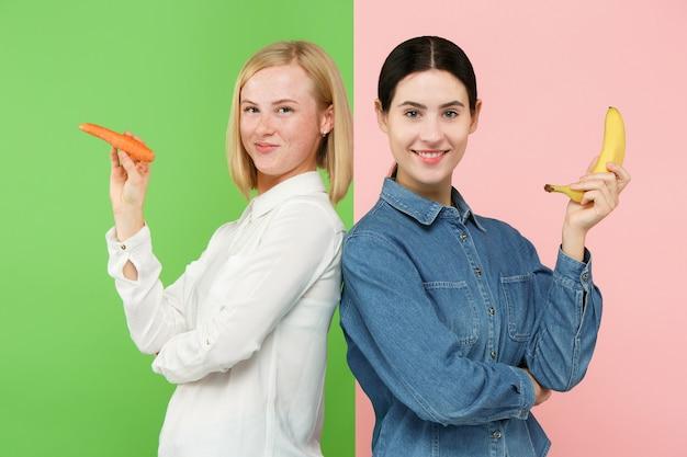 果物と野菜を持つ若い女性の美しいクローズアップの肖像画。健康食品のコンセプトです。スキンケアと美容。ビタミンとミネラル。