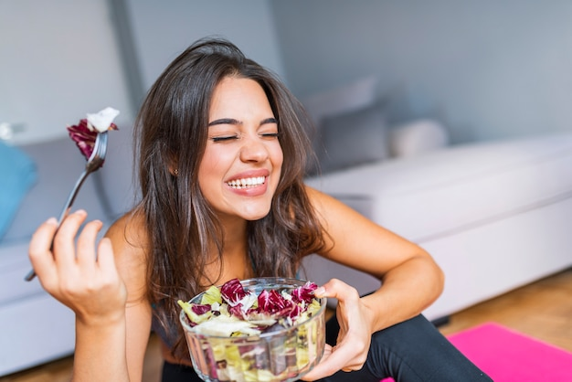 Beautiful close-up portrait of young woman eating salad and vegetables. healthy food conce