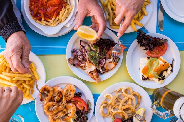 Beautiful close up of table woth gourmet and marine food like fish and chips with hands taking it - group of people eating together - above and top view