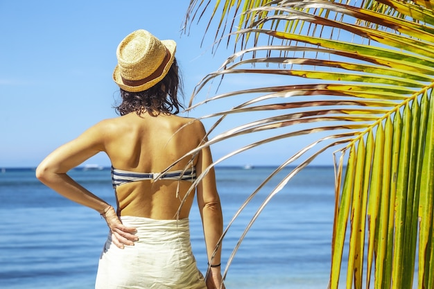 Beautiful closeup of a brunette female in a swimsuit next to a palm against blue lagoon at daytime