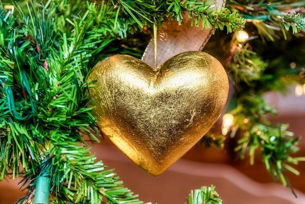 Bellissimo primo piano di un ornamento d'oro a forma di cuore su un albero di natale con luci