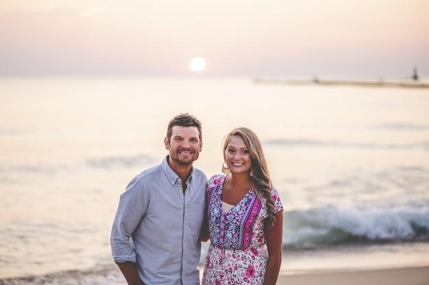 見事な海の景色の前でポーズをとって若いカップルの美しいクローズアップの肖像画