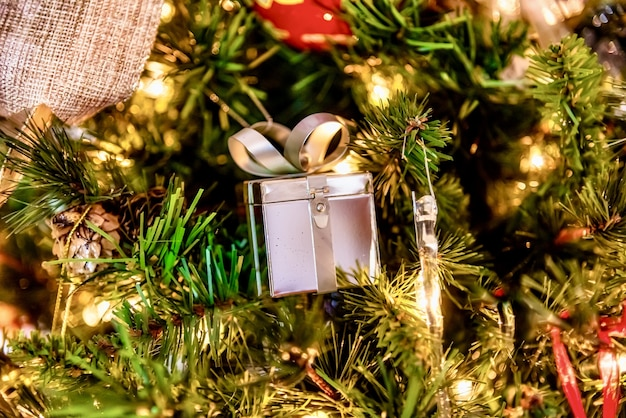 Beautiful closeup of a silver gift ornament  and other decorations on a christmas tree with lights