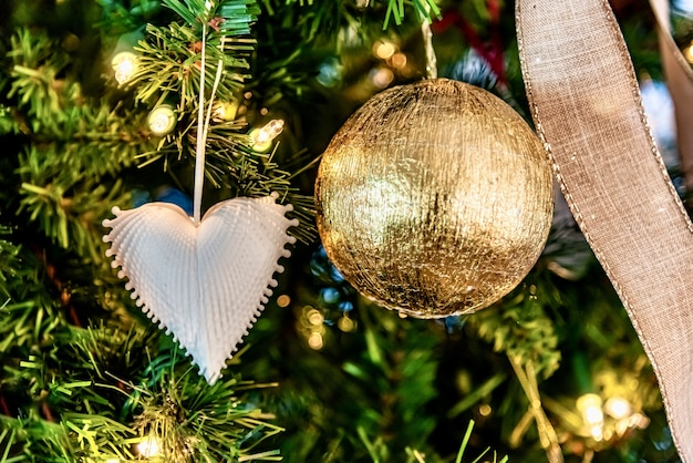 Beautiful closeup of a white heart-shaped ornament and golden ball on a christmas tree