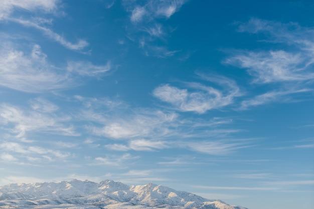 ウズベキスタンの冬の天山山脈の青い空を背景に美しい雲