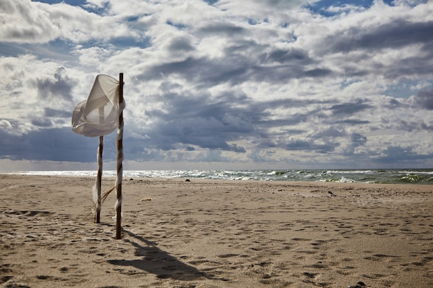 Красивые облака и разорванный ветром свадебный шатер на песчаном пляже. свадьба на пляже