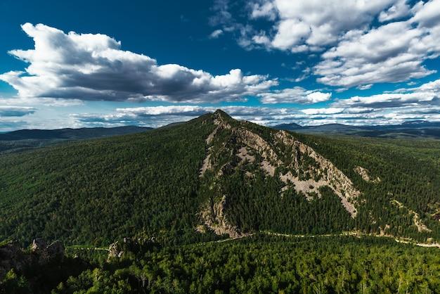 Красивые облака над зеленой горой. гора малый ямантау в башкирии, россия. зеленый лес под голубым небом. лес, горы, небо, облака. девственная природа. охрана природы. бронировать