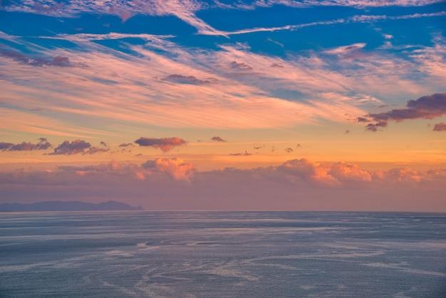 山と海に沈む美しい雲景と劇的な夕日。