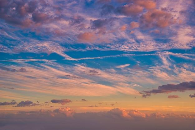 Красивые облака и драматический закат над горами и морем.