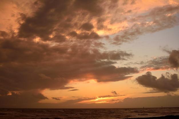 海に沈む夕日の美しい曇り空