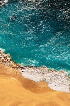 Красивое побережье на островах в индийском океане, вертикальный вид. красивый песчаный пляж с бирюзовым морем. вид сверху на тропический бирюзовый пляж океана. побережье как фон сверху. мальдивы