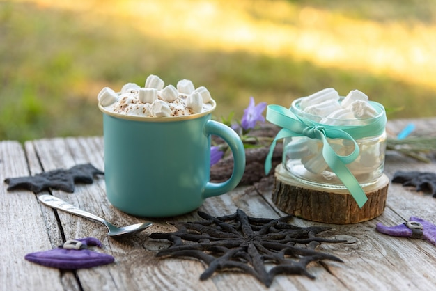 A beautiful coffee drink with small pieces of marshmallow and grated chocolate. on the day of halloween.