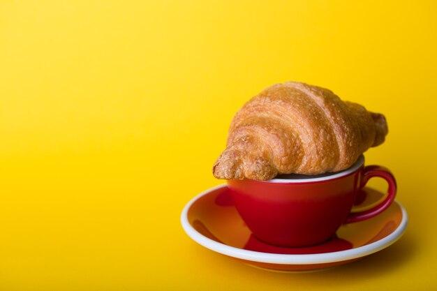 黄色の背景にカプチーノとクロワッサンと美しいコーヒーの赤いカップ