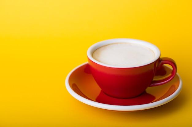 黄色の背景にカプチーノと美しいコーヒーの赤いカップ