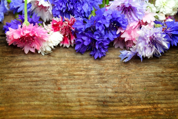 Beautiful colorful background - bright flowers on wooden background