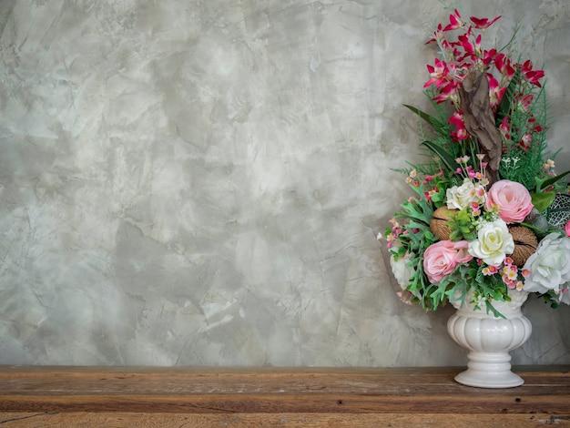 Красивый красочный букет цветов в белом старинном украшении вазы на деревянном столе на фоне бетонной стены в стиле лофт, с копией пространства.
