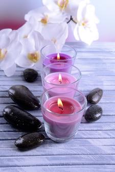 美しいカラフルなキャンドル、スパストーン、蘭の花、色の木製テーブル、