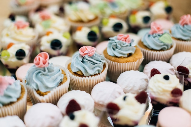 パーティーのケータリングテーブルの美しいカラフルなカップケーキとクリームデザート