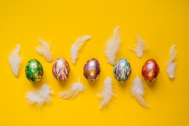 아름 다운 화려한 부활절 배경 화면, 노란색 배경에 그려진 부활절 달걀 andwhite 깃털 배너.