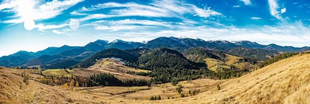 Красивые красочные леса, покрывающие карпаты, и небольшую деревню на фоне теплого осеннего неба.