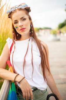 Beautiful colorful girl with lgbt flag on her cheek posing outdoor