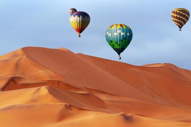 Красивые красочные воздушные шары и драматические облака над песчаными дюнами в пустыне намиб