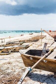 Красивый красочный пейзаж с гамаком, висящим на ладони, и лодками в океане на заднем плане